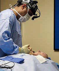 A surgeon performing a facelift procedure