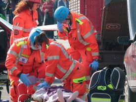 EMTs performing CPR on a car-crash victim