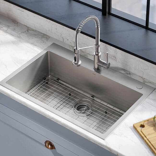 The faucet above is deck mounted directly to the sink's rim. See Kraus' Stark dual-mount, single-bowl stainless steel drop-in sink with its pull-down commercial kitchen faucet.