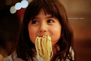 A kid enjoying spaghetti pasta