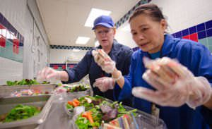 Registered Dietitian Sandra B. O'Connor (L) prepares trays of salad for lunch for kids at Nottingham Elementary School in Arlington, VA.