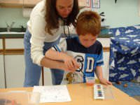 An occupational therapist working with a kid to teach fine motor skills