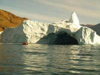 Rafters approaching an iceberg cave in North East Greenland