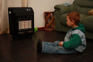A kid fascinated by a gas heater
