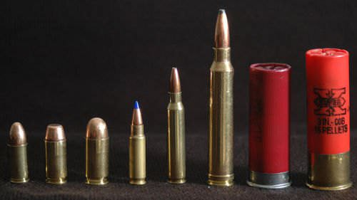 A line-up of pistol and rifle cartridges. From left to right: 9 mm Luger Parabellum, .40 S&W, .45 ACP, 5.7x28mm, 5.56x45mm NATO, .300 Winchester Magnum, and a 2.75-inch and 3-inch 12 gauge.