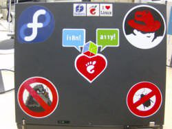 "Laptop stickers showing Fedora, Red Hat, ""no bugs"", and ""no worms. The center one is GNOME Love with the internationalization (i18n) and accessibility (a11y) and a GTK+ cube mapping to those."