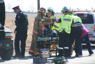 Paramedics and fire fighters attend to a car crash victim