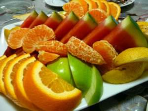 A fruit platter with apples, oranges and watermelons