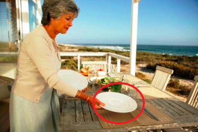 She lays the plate (direct object) on the table