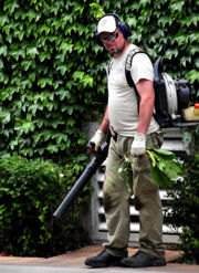Man with a gas leaf blower