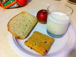 A Nutrisystem meal comprising of a chocolate chip scone, apple, rye bread, and 8oz milk