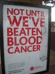 A blood cancer-awareness advertisement at a bus stop