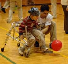 A physical therapist working with a kid.