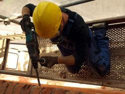 Hammer drill drilling through brick