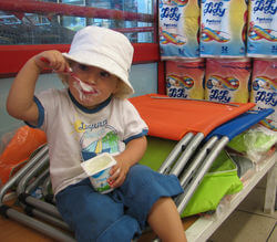 A 2 yr old eating Yogurt at a supermarket