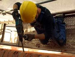 A construction worker hammer drilling a brick wall
