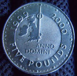 This special £5 coin was made in 1999, before the turn of the century (from the 20th to 21st centuries / AD 1999 - 2000). On one side it marks GMT (Greenwich Mean Time) with the line going through Greenwich.