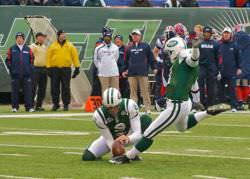 A NY Jets player kicks a ball at the beginning of a football game