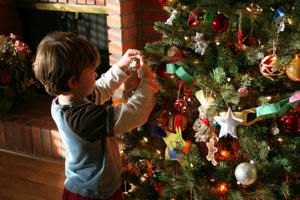 A kid decorating a Christmas tree