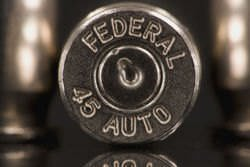A close-up of .45 ACP which shows what the primer cap looks like after the round has been fired and ejected from the chamber. The depression in the center is where the firing pin struck the primer cap.